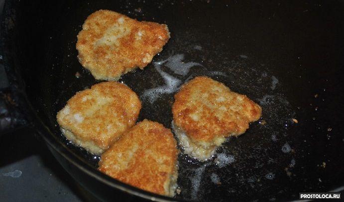 Выложить запанированные кусочки курицы на сковороду.