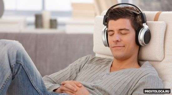 Young man relaxing with headphones, listening to music with eyes closed, smiling.